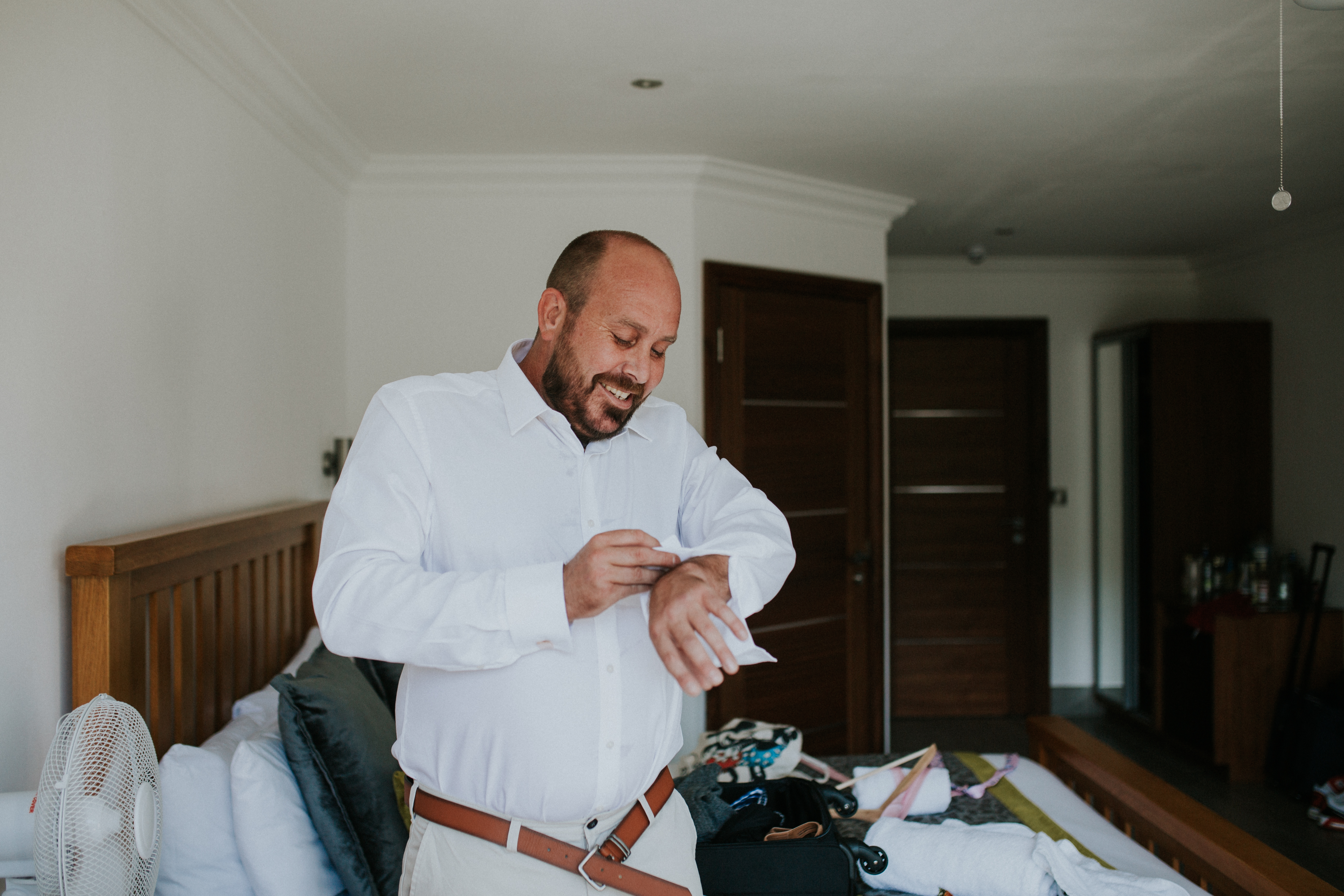 groom doing cufflinks